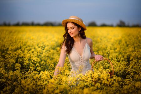 Summer mood. Young beautiful woman picks yellow flowers in a field.
