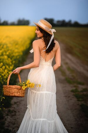Summer mood. A beautiful young female walks along a blooming yellow field with her back to the camera.