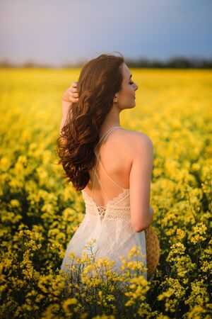 Summer mood. A young beautiful caucasian woman in a white dress is standing in a blooming yellow field back to camera.