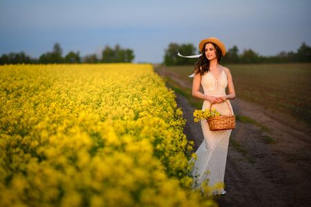 Summer mood. A young beautiful caucasian woman in a white dress is standing in a blooming yellow field.