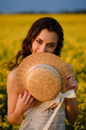 Portrait of a beautiful young smiling woman in a blooming yellow field. Summer mood.