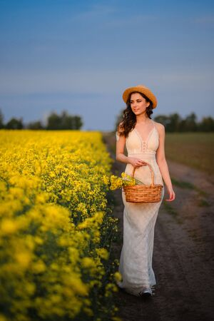 Summer mood. Young beautiful caucasian woman in a white dress is walking in a blooming yellow field. Full height portrait. Imagens