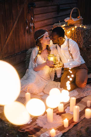Boho style wedding. African groom and Caucasian bride sit embracing on a plaid surrounded by garlands and candles. Summer evening.