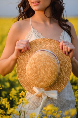 Young beautiful woman holding a hat in front of her hands while standing in a yellow flowering field. Cropped portrait. Summer mood.