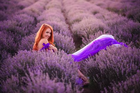 Happy young red-haired woman sitting in lavender field at sunset