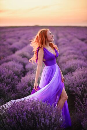Summer mood. Happy young red-haired woman in luxurious dress standing in lavender field at sunset