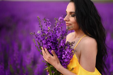 Beautiful young woman with closed eyes in a yellow dress holds in her hands a bouquet of purple flowers. Close-up.