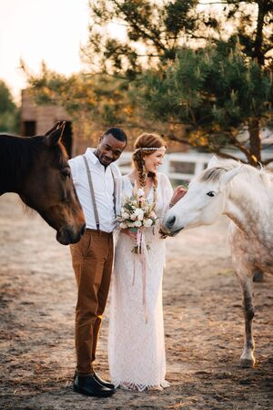 Happy african bridegroom and caucasian bride stand on a ranch with horses. Imagens
