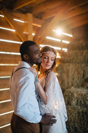 Newlyweds in the style of boho. African groom hugs a Caucasian bride in a barn in the sun. Flare effect.