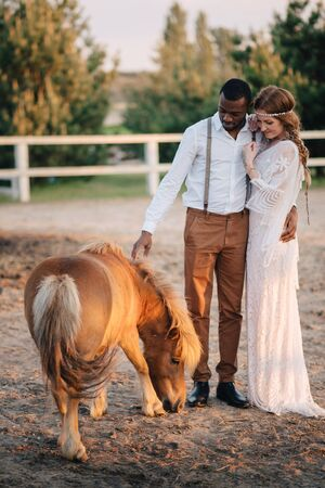 Happy african groom and caucasian bride stand on a ranch near pony.