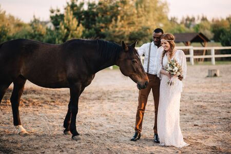 Happy african bridegroom and caucasian bride stand on a ranch near a horse.