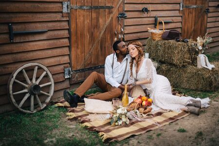 Boho style wedding. African groom and Caucasian bride are sitting on a plaid near the barn.