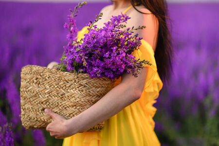 A woman in a yellow dress holds in her hands a wicker basket with purple flowers. Close up.