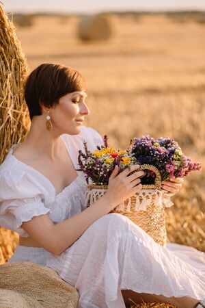 A young short-haired woman sits near a haystack holding a basket of flowers in her hands. Rural life.