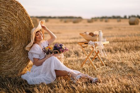 Summer day. A young short-haired woman sits near a haystack on a warm summer day. Imagens