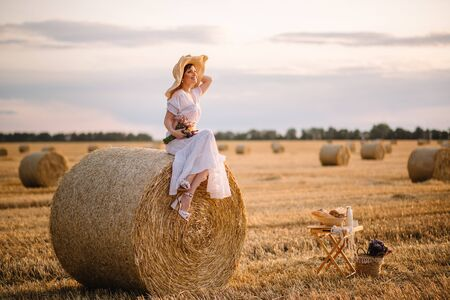 A young woman in a white sundress sits on a haystack on a mown field on a warm summer day.