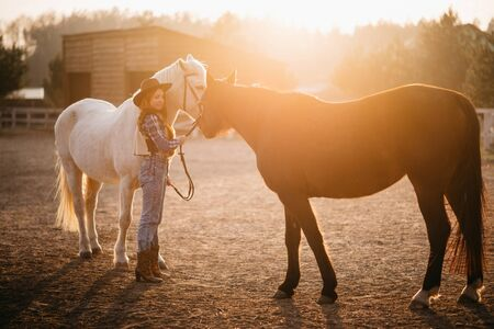 A young cowgirl woman stroking a horse in the sunset at her ranch. Flare effect.