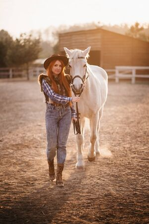 A young woman farmer leads a horse in a corral on a ranch at sunset in the backlight. Full-length portrait. Imagens