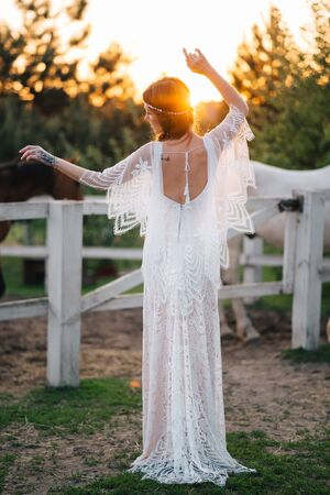 Boho young bride stands with her back to the camera in the sunset light. Imagens