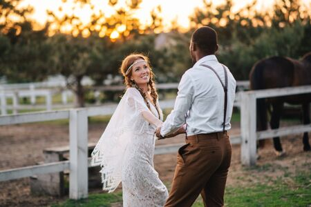 An interracial couple of newlyweds in the style of boho walk on a ranch at sunset. Soft focus. Imagens