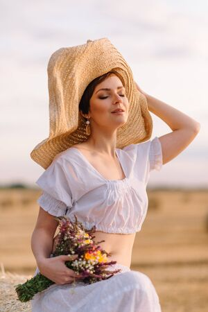Summer mood. Portrait of a young beautiful woman in a hat in a field on a sunny day. Close up. Imagens