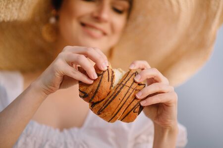 Young woman in a hat breaks off a piece of bun, close-up of hands. Selective focus. Imagens