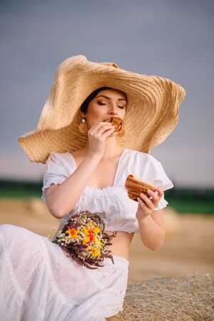 Summer mood. A young woman in a white sundress sits on a haystack and eats a bun in the field.