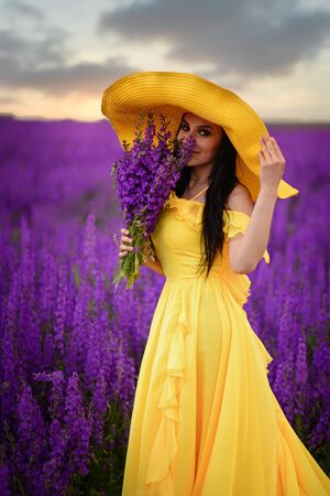 A young smiling woman in a yellow dress and hat is standing in a blooming purple dress.