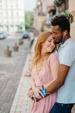 Interracial Relations. An African man and a Caucasian woman stand embracing on a city street. Imagens