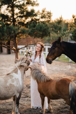 A laughing young bride in a boho style stands surrounded by horses on a ranch.