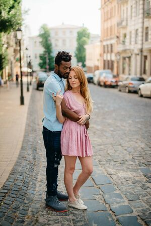 Interracial Relations. An African man and a Caucasian woman stand embracing on a city street. Full height portrait. Imagens