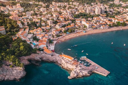 The ancient Mediterranean resort town of Petrovac in Montenegro, aerial view on a sunny day. Imagens
