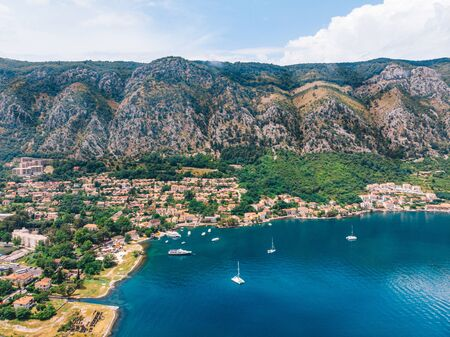 Bay of the Mediterranean Sea with yachts on the background of high mountains on a sunny day. Aerial view. Kotor, Montenegro.