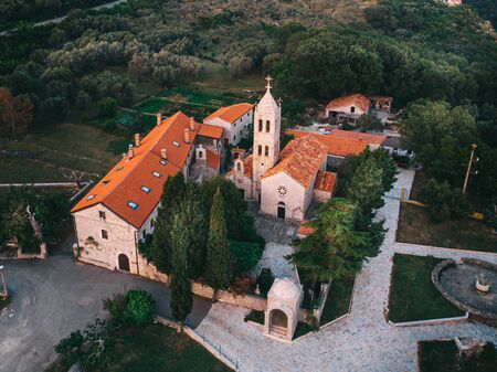 Medieval monastery in the mountains in the Mediterranean. Aerial view at sunset.