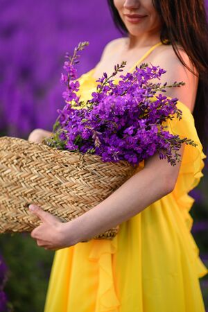 A woman in a yellow dress holds in her hands a wicker basket with purple flowers. Cropped shot.