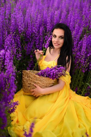 Beautiful young woman in a yellow dress sits in a field of purple flowers.