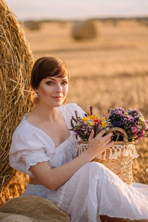 A young short-haired woman sits near a haystack holding a basket of flowers in her hands. Close up.