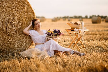 A young short-haired woman sits near a haystack on a warm summer day. Imagens