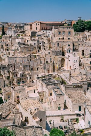 View of the dense buildings of stone houses in the medieval city of Matera, Italy. Sunny day.