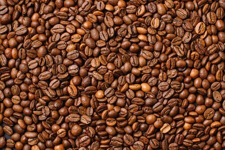 Background from a variety of roasted arabica coffee beans, top view.
