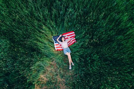 US Independence Day. Joyful teenager girl lies in the grass on the USA flag. Top down view.