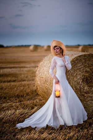 woman in wedding dress stands in field with lamp in her hands in evening Imagens