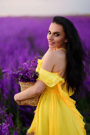 Beautiful young woman in a yellow dress holds in her hands a basket with purple flowers. Close-up portrait.