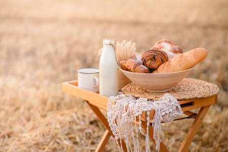 Composition from an assortment of fresh bread on a background of a mowed field of wheat.