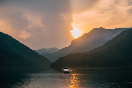 Calm landscape overlooking a mountain lake and a lone boat during sunset.