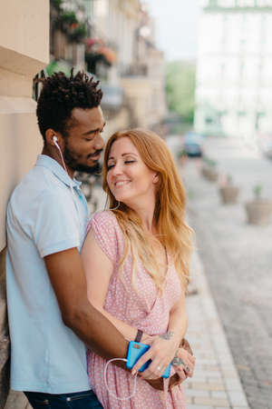 Young happy couple, Caucasian woman and African man, listening to music together with headphones on a city street on a sunny day.