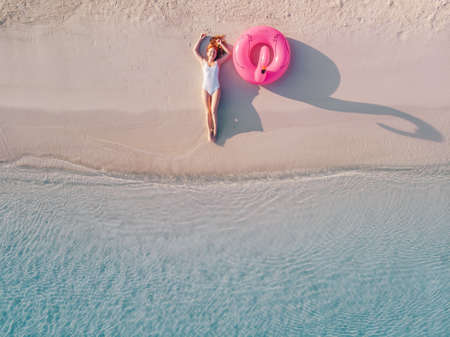 Young happy woman in a swimsuit lies near an inflatable flamingo on the beach, top-down view.