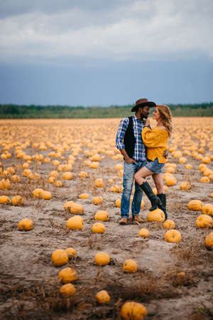 Happy couple stands in pumpkin field and hugs Full-length portrait.