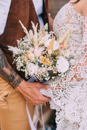 Wedding bouquet close up. Newlyweds in boho style are embracing, the bride is holding flowers in her hands.
