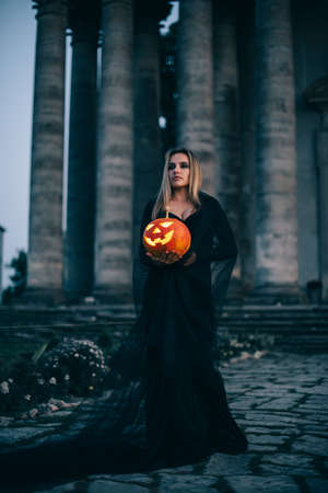 A young woman witch in black clothes stands near the old castle and holds in her hands a luminous pumpkin with a terrible face. Full-height portrait. Imagens